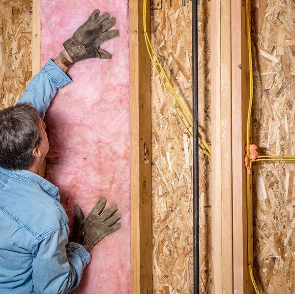 Construction worker puts up some insulation between studs